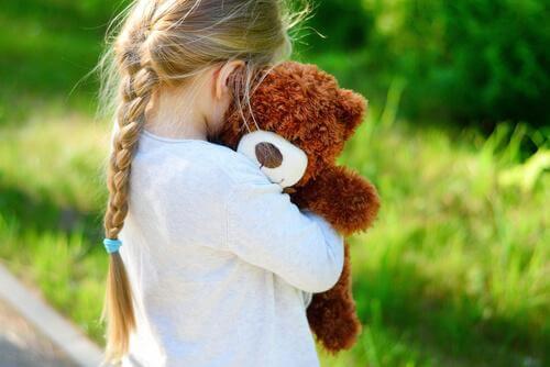 lasten hyväksikäyttö: tyttö halaa nallea