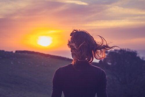 nainen katselee aurinkoa