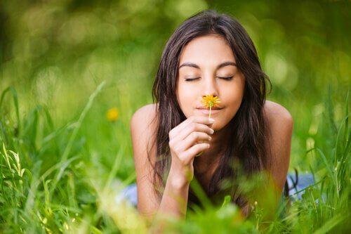 nainen haistaa kukkaa