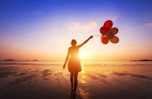 nainen on rannalla kädessään ilmapalloja