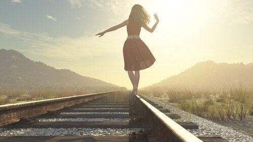 nainen kävelee junanraiteilla