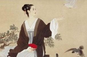 nainen odottaa että kyyhkynen lentää hänen kädellensä