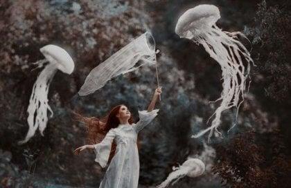 tyttö ottaa haavilla meduusoja kiinni