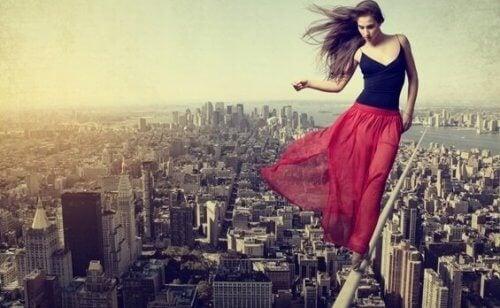 nainen kävelee nuoralla kaupungin yllä