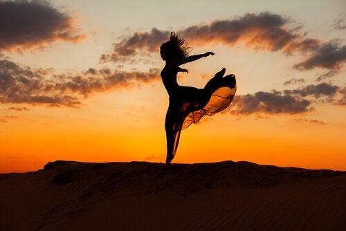 nainen tanssii auringonlaskussa