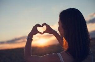 nainen muodostaa sydämen käsillään