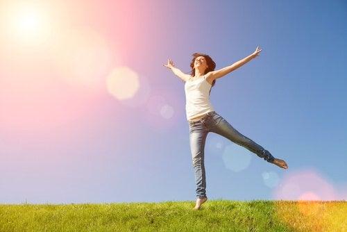 nainen hyppää onnellisena nurmikolla