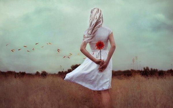 nainen kantaa kukkaa selkänsä takana