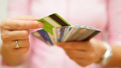 nainen valitsee yhden kaikista muovikorteistaan