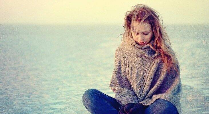masentunut äiti istuu yksin rannalla