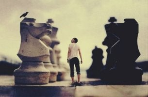 mies on jättimäisten shakkinappuloiden keskellä