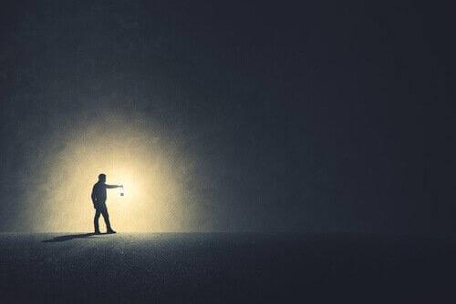 miehellä öljylamppu pimeässä