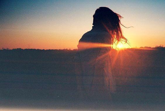 nainen on yksin auringonlaskussa
