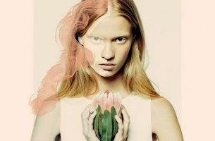 vihaisen näköinen nainen jolla on kukka
