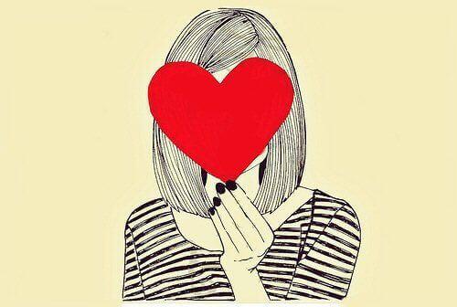 nainen pitää sydäntä kasvojensa edessä