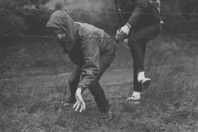 miehet käyttävät sinnikkyyttä päästäkseen aidan toiselle puolen