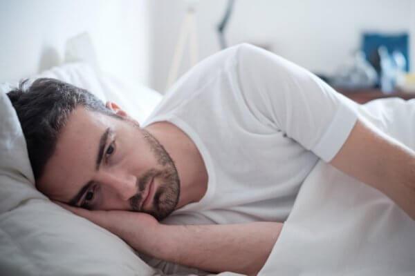mies makaa surullisena sängyssään