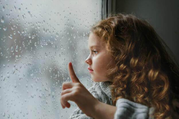 tyttö katselee ulos sateeseen