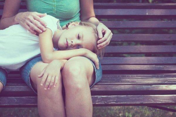 tyttö makaa äidin sylissä