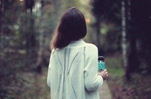 nainen kävelee metsässä pullo kädessään