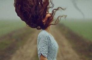 nainen heilauttaa hiuksiaan