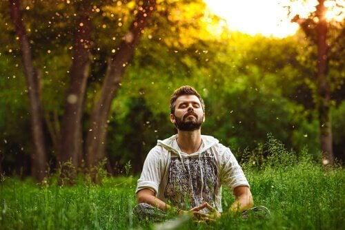 mies istuu ulkona ja meditoi