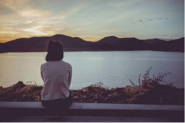 nainen istuu ja katsoo järvelle