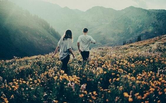 ystävät kävelevät kukkakedolla