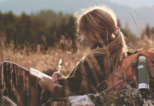 nainen kirjoittaa ulkona päiväkirjaa