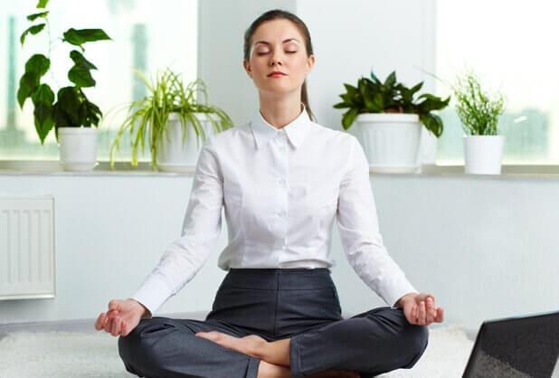nainen meditoi ja hengittää syvään