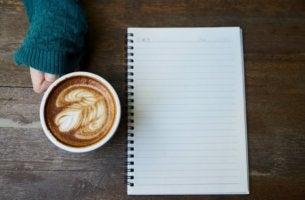 nainen pitelee kahvikuppia ja lehtiötä edessään