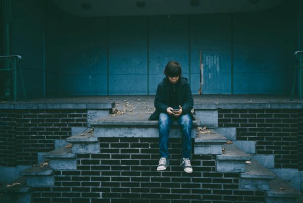 poika istuu yksin ja katsoo puhelintaan