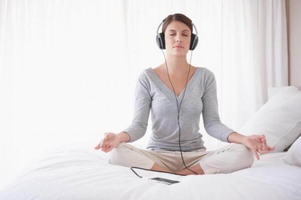 nainen meditoi ja kuuntelee jotain