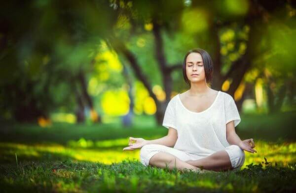 nainen meditoi puistossa
