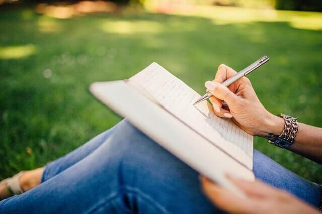 nainen kirjoittaa päiväkirjaa
