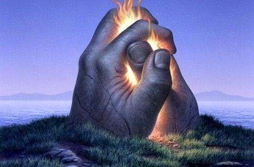kädet työntyvät maasta ja ovat tulessa