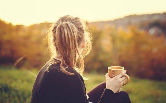nainen istuu ulkona ja juo kahvia