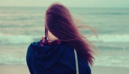nainen rannalla tuulessa