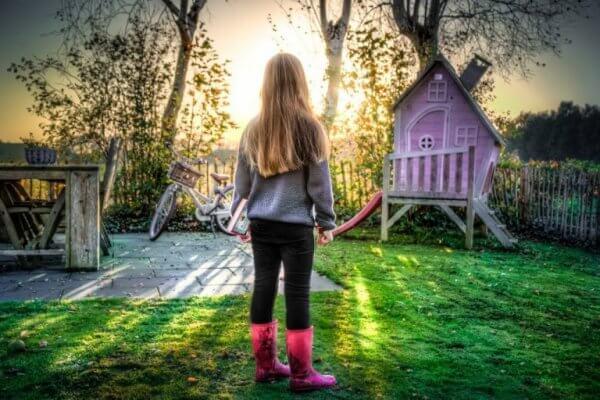 tyttö seisoo puutarhassa