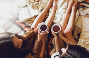 ystävät juovat teetä sängyssä