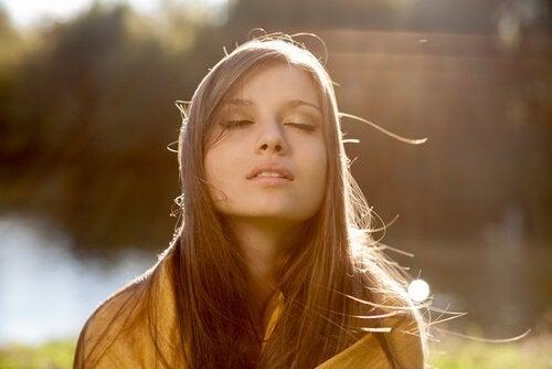 nainen tekee hengitysharjoitusta luonnossa