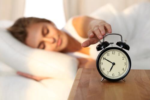 nainen sammuttaa herätyskellon