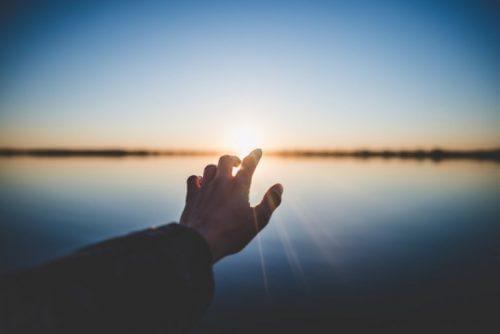 käsi yrittää koskettaa aurinkoa