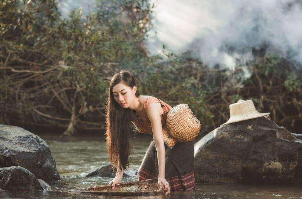 nainen puuhaa joella
