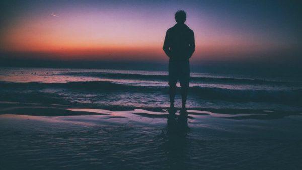 mies rannalla auringonlaskussa