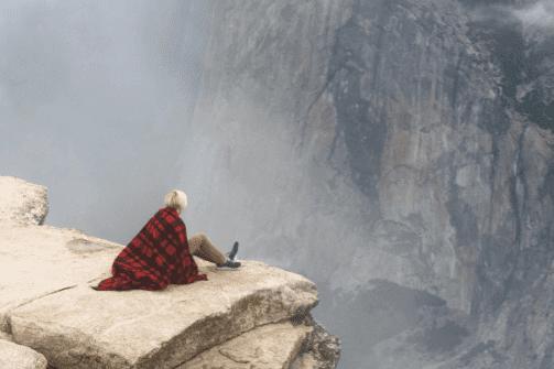 nainen korkealla kalliolla