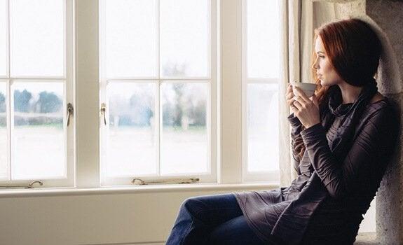 nainen juo teetä ikkunan edessä