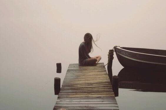 nainen istuu yksin laiturilla