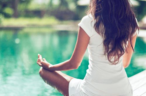nainen meditoi veden äärellä