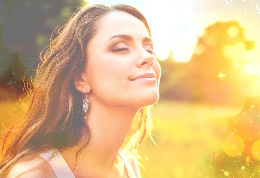 nainen antautuu, hymyilee ja nautiskelee